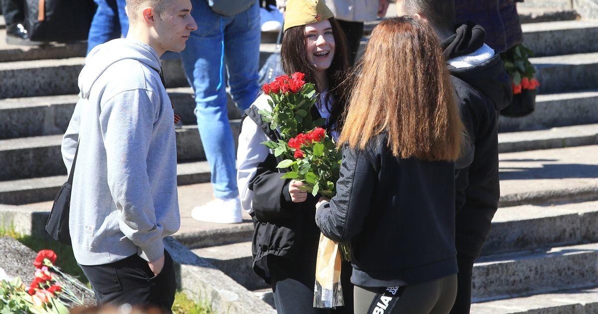 Люди выстраиваются в очередь, чтобы возложить цветы к монументу в Тарту